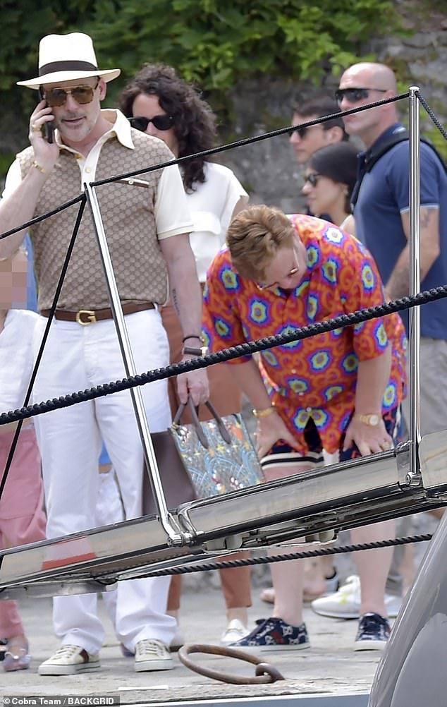 Rest: Elton stopped to stretch and catch his breath before boarding the boat