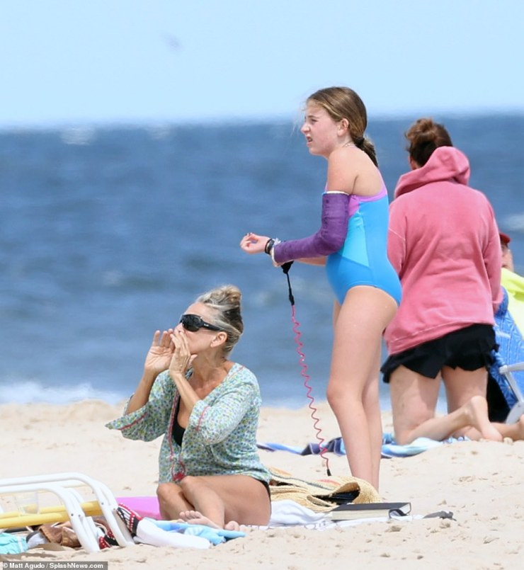Busy on the beach: Sarah did not seem to sit still as she talked to her family