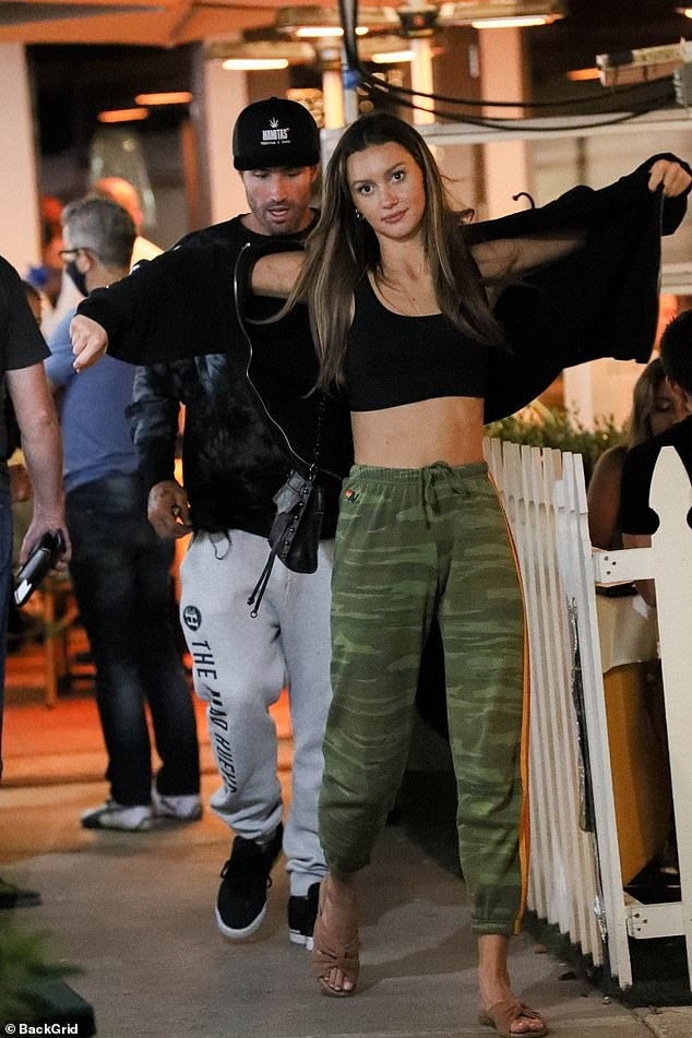 Date night: The 37-year-old reality star's companion showcased her taut tummy in a black sports bra beneath a matching hoodie and camouflage sweatpants