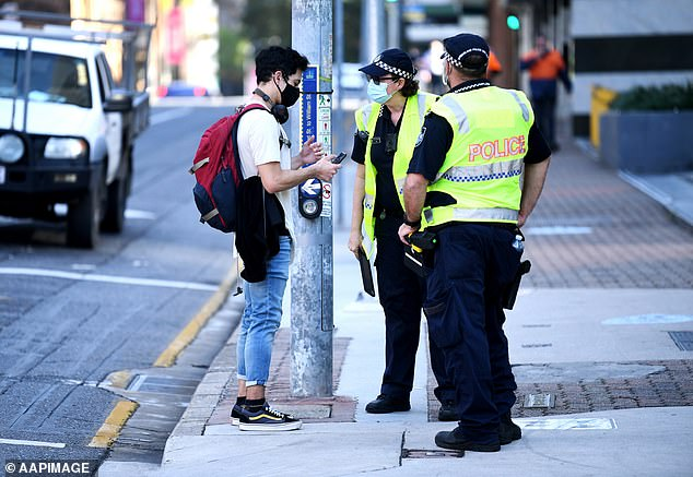 Police check a member of the public for compliance with lockdown orders in central Brisbane on Monday morning