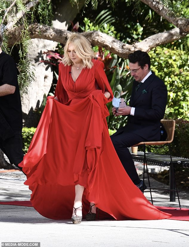 Red hot: Kerri-Anne looked stunning in a floor-length red gown with a sweeping skirt, low-cut back and V-neckline