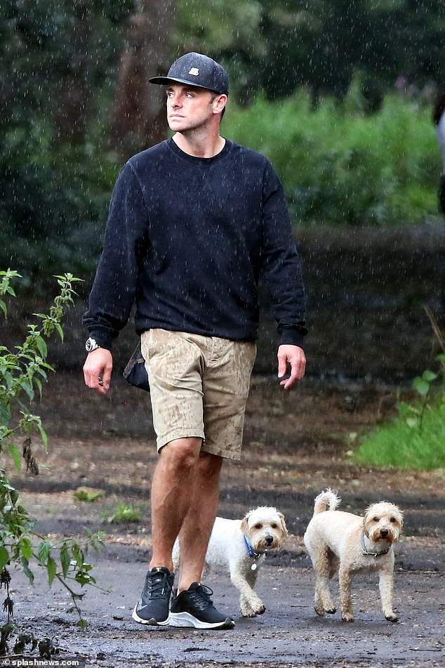 Out and about:Ant McPartlin was on dutiful dog-walking duties on Sunday as he stepped out in the drizzle with his pet pooches