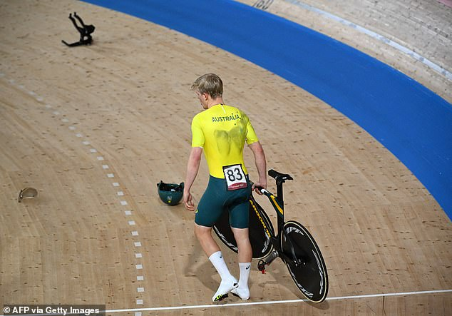 Australia's Alexander Porter carries his bicycle after crashing during the men's track cycling team pursuit qualifying event during the Tokyo 2020 Olympic Games