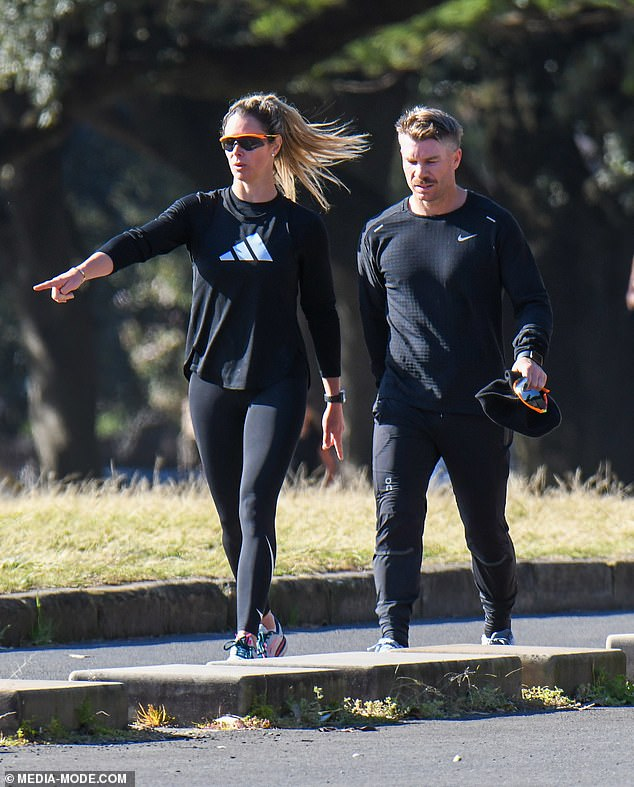 Keeping fit:Cricket WAG Candice Warner and her husband David wore similar outfits as they went for a jog during Sydney's lockdown on Monday