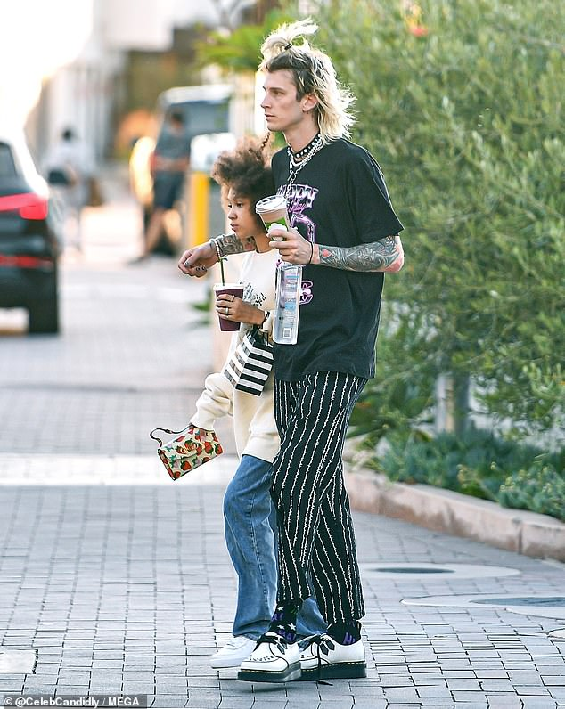 Sweet: MGK wrapped her arm around her baby girl while juggling a water bottle and a delicious SunLife smoothie