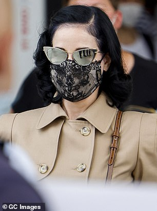 Lingerie-inspired face mask:The former spouse of Marilyn Manson wore her raven locks in her iconic style, swept to the side with curls hanging behind her ears