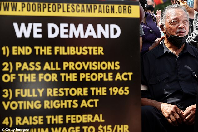 Jackson stands beside a sign outlining the campaigners' demands. They want them to be passed by Congress before August 6 - the 56th anniversary of the Voting Rights Act