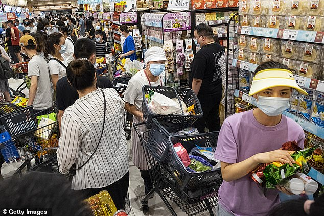 Panic buyers wearing protective face masks line up at the supermarket checkout in Wuhan on Monday