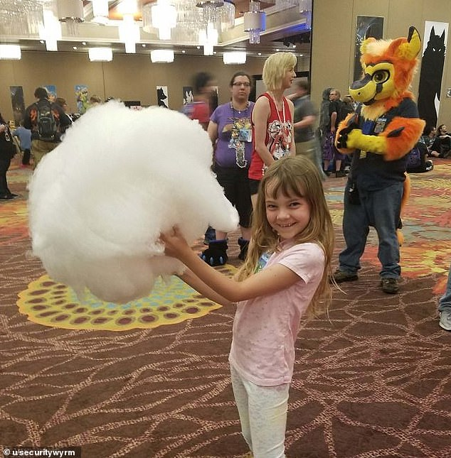 She's not complaining! This little girl looked delighted when her mother ordered a 'child-sized' swirl of cotton candy at a convention in the US