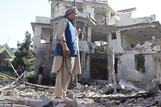 Afghan security officials stand guard outside the house of acting Defense minister Gen. Bismillah Mohammadi, after an overnight explosion and attack, in Kabul on Wednesday