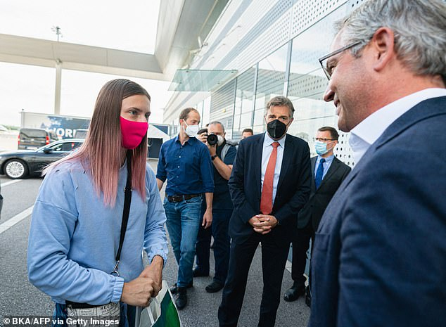 Belarusian Olympic athlete Krystsina Tsimanouskaya, wearing a pink face mask, a blue jumper and jeans, was seen speaking to Austria's deputy environment minister Magnus Brunner after she landed in Vienna
