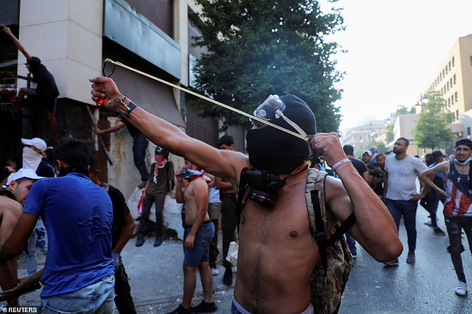 A protestor uses a slingshot outside the parliament as a crowd forms to vent its fury at the government