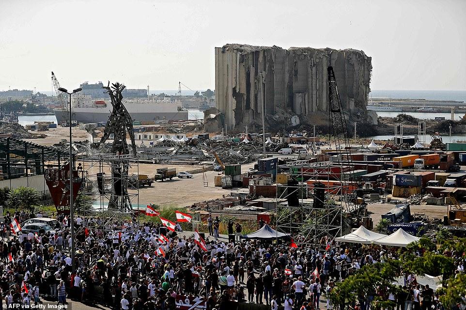 Demonstrators gather near the damaged grain silos outside the port of Lebanon's capital Beirut on August 4