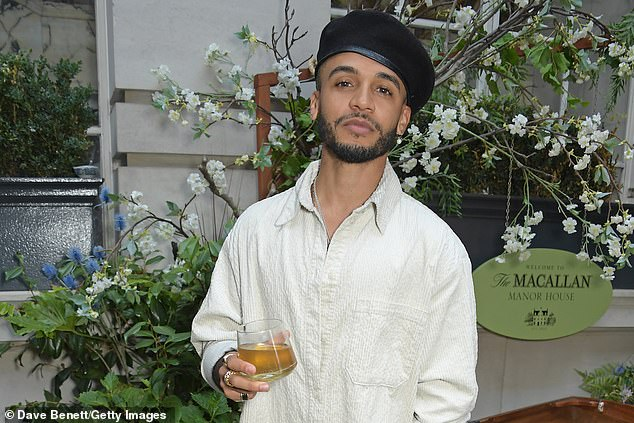 Party time: JLS star Aston Merrygold, 33, showed off his edgy style in a black beret to match his dark beard as he held a glass ofMacallan whiskey in his hand