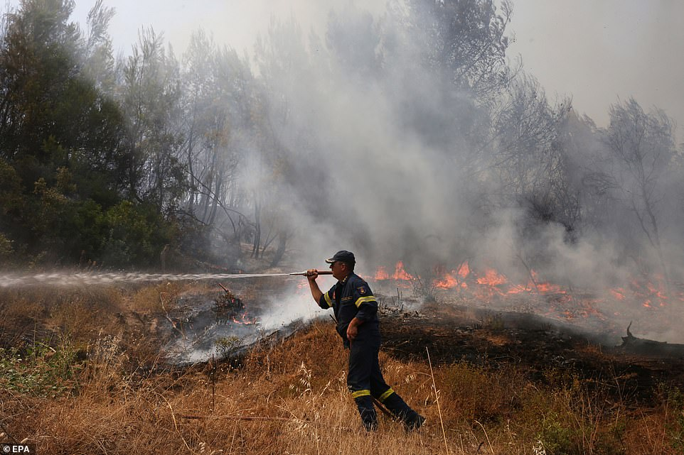 A fireman douses flamesin Koskinas village in the area of Olympia,Peloponnese