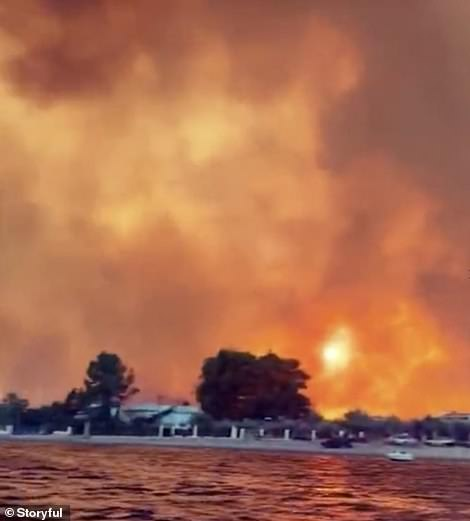Smoke rises in the air above the beach as fire rips through coastal villages