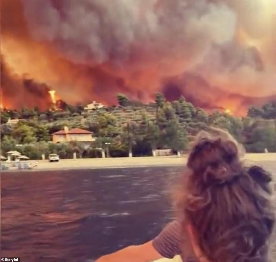 Footage shows the people looking back at the island as the flames lick around villas which line the beaches