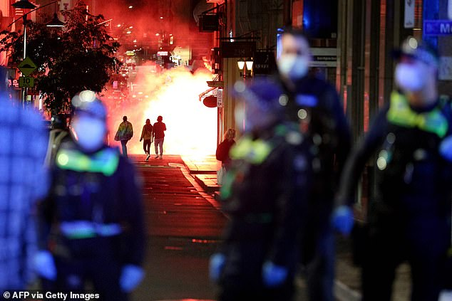 A large ball of fire is captured in the background as chaotic anti-lockdown protests erupted in Melbourne on Thursday night (pictured) with hundreds taking to the streets