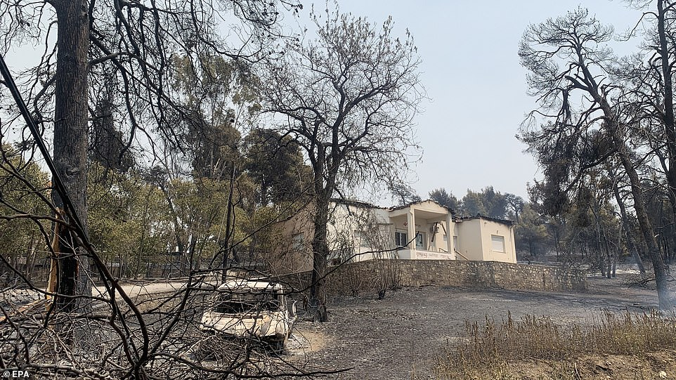 A burnt out car outside a scorched house in the Rovies area of Evia island on Thursday
