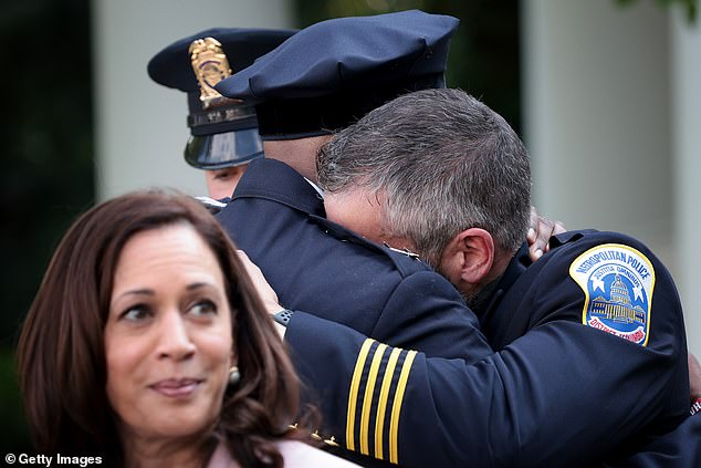DC Metropolitan Police Officer Michael Fanone (R) hugs DC Metropolitan Police Chief Robert Contee (C) after Joe Biden delivered remarks honoring law enforcement in the Rose Garden