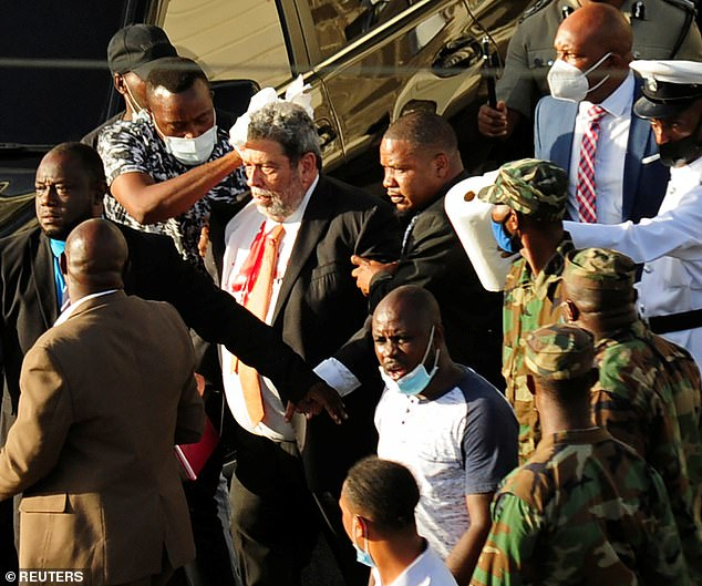 The crowd blocked the Prime Minister's vehicle, forcing him to enter the parliament on foot. Above, Gonsalves is rushed from the scene