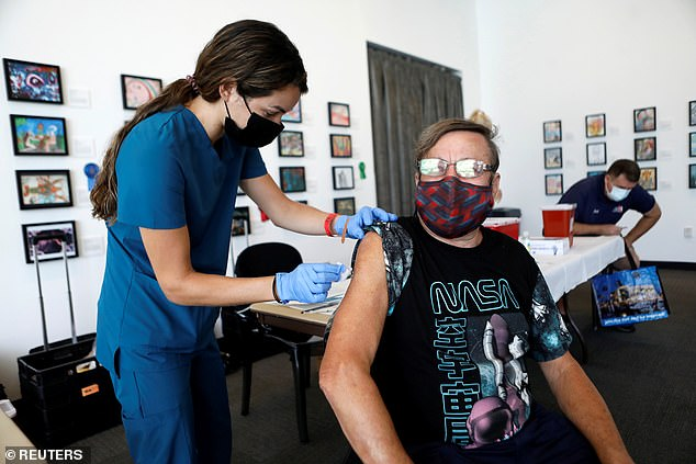 More than 70% of the unvaccinated Covid survivors in the study contracted the virus compared to 20% of those fully vaccinated. Pictured:Amanda Tetlak, a registered nurse, administers a dose of the Pfizer-BioNTech COVID-19 vaccine to Fred Miller in St Petersburg, Florida, August 2021