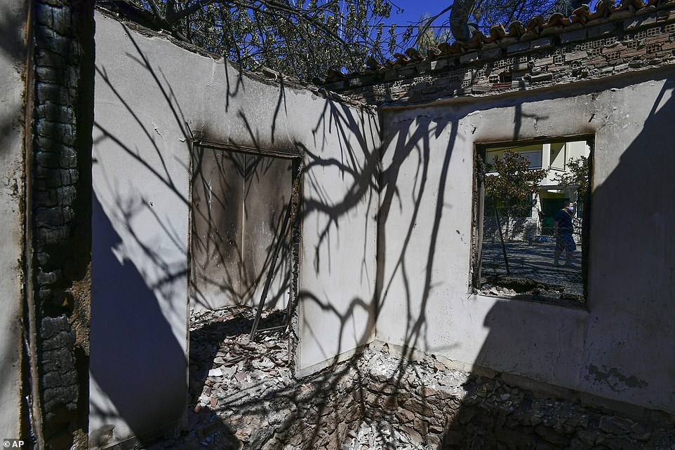 The remains of a burned house are seen in Kryoneri in Athens this morning