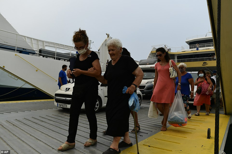 Evacuees are seen disembarking from a ferry which rescued them from Evia island as fires tear through it