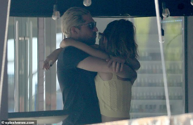 Cute: The couple shared a cuddle as they waited for their drinks order