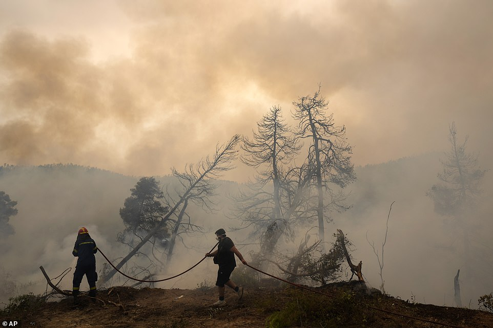 A firefighter tries to extinguish the flames as a local holds a water hose during a wildfire at Ellinika village on Evia island