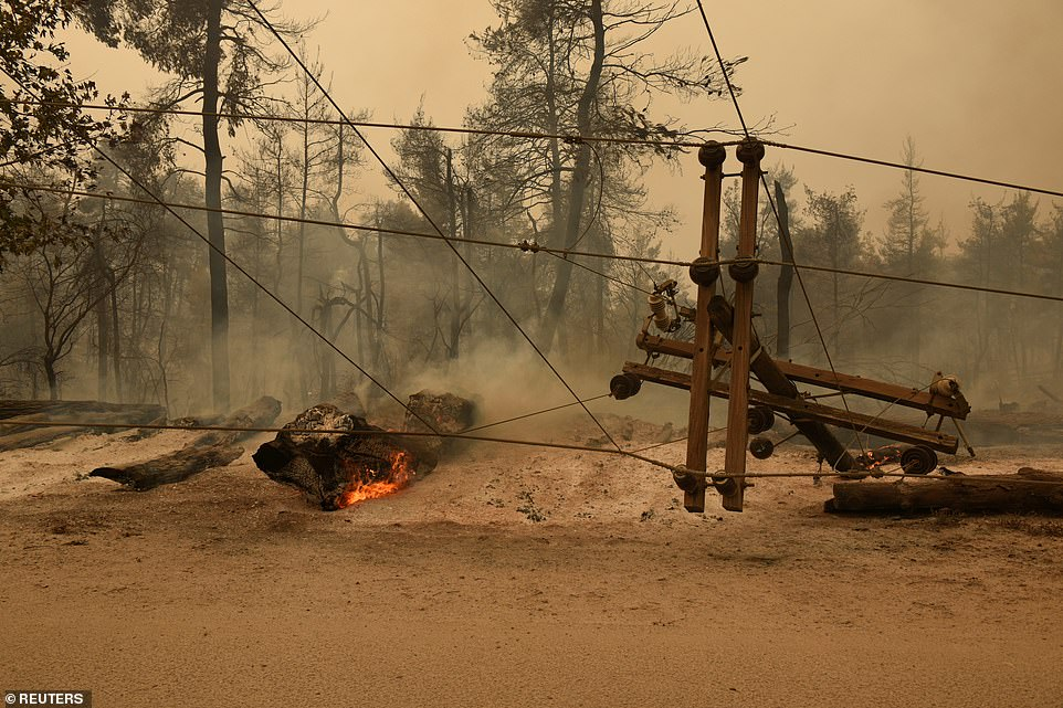 A destroyed electricity pole lays on the ground as a wildfire burns near the village of Ellinika, on the island of Evia