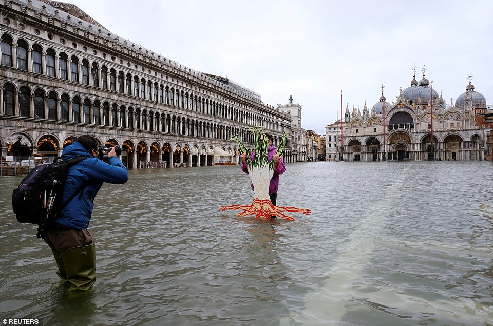A person posing for a photo in the Piazza in December last year when the city experienced deadly flooding