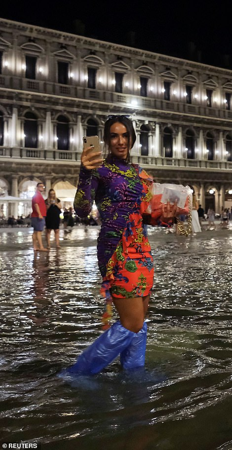 A young woman wades through the water with plastic wrapped around her boots