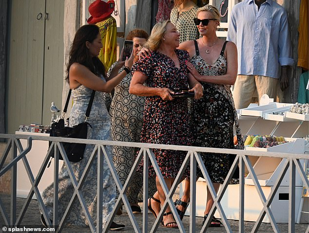 Looking good:Charlize was sartorially in sync with her mother Gerda on the outing, who also opted for a dark floral dress which boasted a V-shape neckline