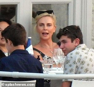 Loving life: Charlize put on an animated display as she sat down for lunch with her friends and family