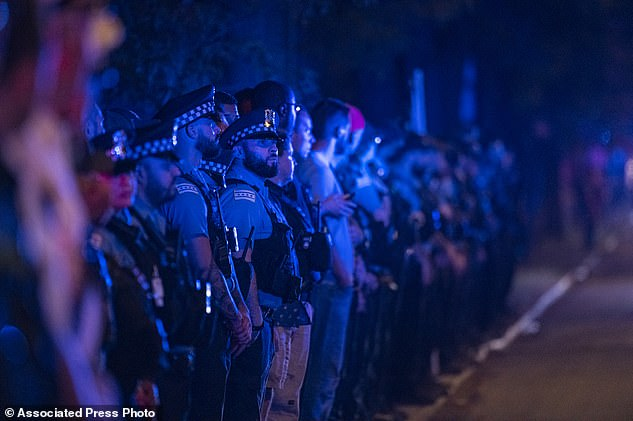 Chicago police officers stand at attention as a procession for a police officer who was shot and killed earlier during a traffic stop at 63rd and Bell drives by
