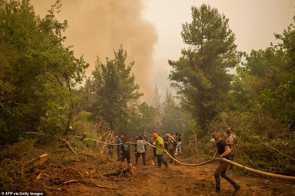 Firefighters and local volunteers took part in efforts to extinguish the flames near the village of Avgaria, on Evia Island, Greece, on Tuesday