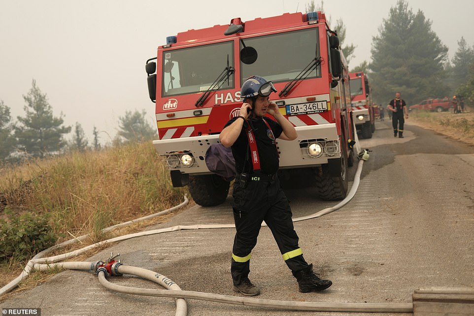 A firefighter from Slovakia adjusts his helmet as he prepares to tackle flames on Greece's Evia Island on Tuesday morning