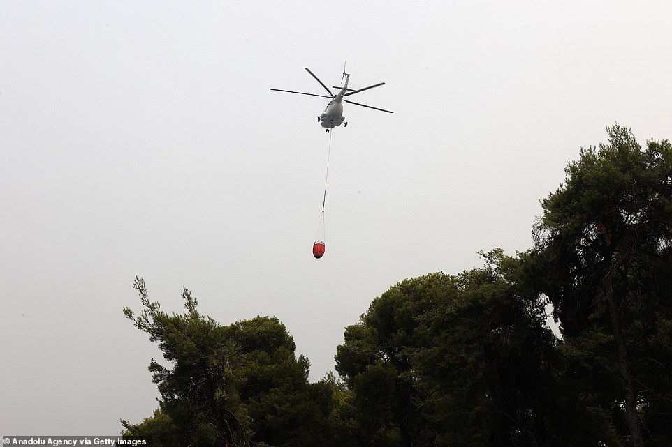 A helicopter responds the wildfires in the island of Evia, Greece on Tuesday as firefighters braced for a pick up in winds from the afternoon which could cause more flare ups on Greece's second largest island