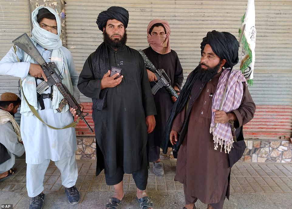 Taliban fighters pose with their weapons in the city of Farah, western Afghanistan, which was captured on Tuesday