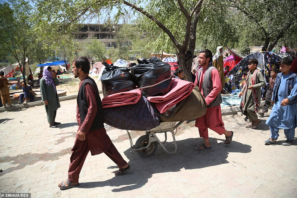 Afghan displaced people who fled from their homes during the fighting carry their belongings in a public park in Kabul