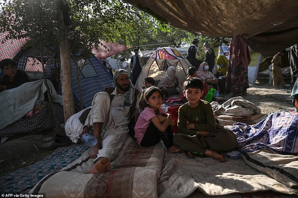 Afghan refugees sit in a camp in the capital Kabul, where thousands of people have fled fighting in the rest of the country