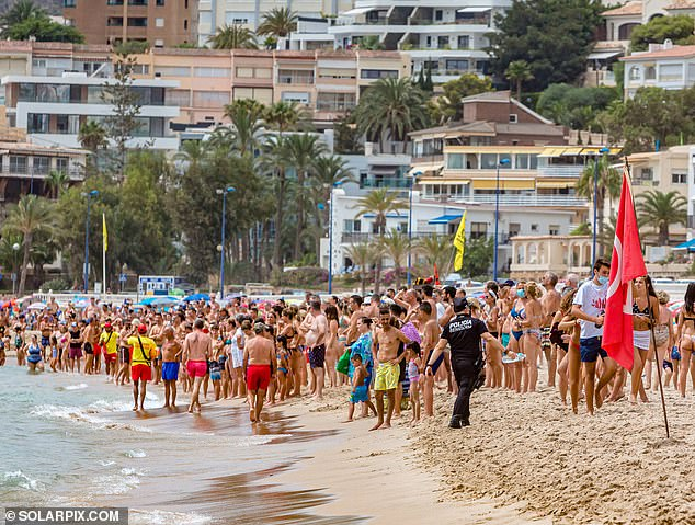 Police officers who were called to the scene on Thursday can be heard telling the beachgoers to stand back, before the shark eventually swam back into the shallow waters