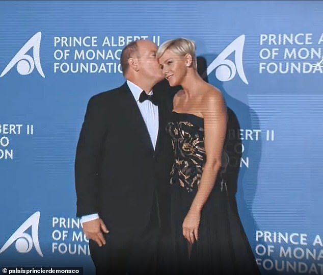 A kiss for the princess: Monaco's royal palace has released a video celebrating Prince Albert and Princess Charlene's joint engagements as the couple spend yet another month apart. Pictured, Albert kisses Charlene at the 2017 Prince Albert II of Monaco Foundation Gala