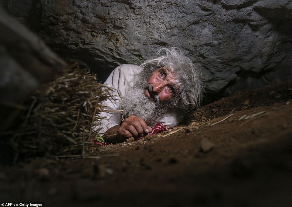 Hermit Panta Petrovic, 70, demonstrates how he leaves his bedroom in his tiny mountain cave houseon the forested Stara Planina mountain in Serbia