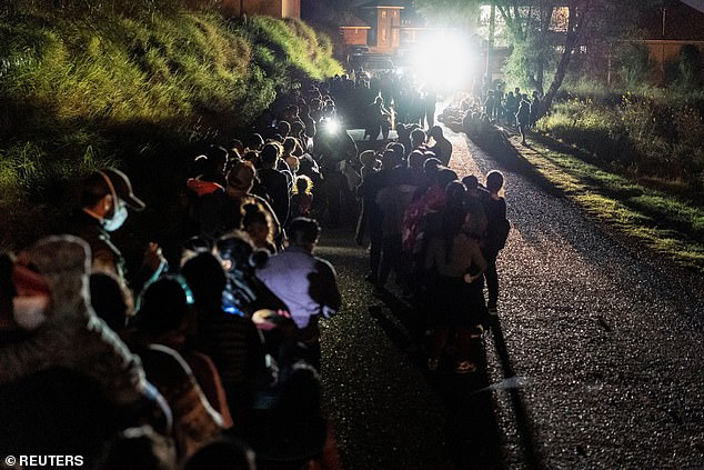 A fresh batch of asylum-seeking migrants lined up to be processed by Border Patrol after crossing the Rio Grande Valley into Roma, Texas in the early morning hours of Thursday