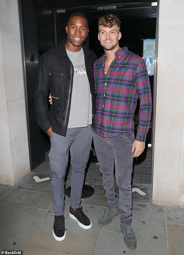 Pals: Hugo, who looked casual for the outing in black skinny jeans and a checked shirt posed for a photo with fellow love islander Aaron Francis, 24