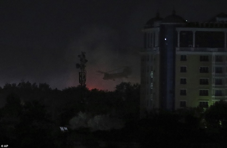 A U.S. Chinook helicopter flies near the U.S. Embassy as smoke rises in Kabul, Afghanistan, late on Sunday night