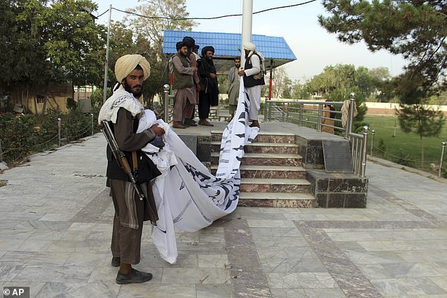 Taliban fighters raise their flag at the Ghazni provincial governor's house, in Ghazni, southeastern, Afghanistan, Sunday, Aug. 15, 2021
