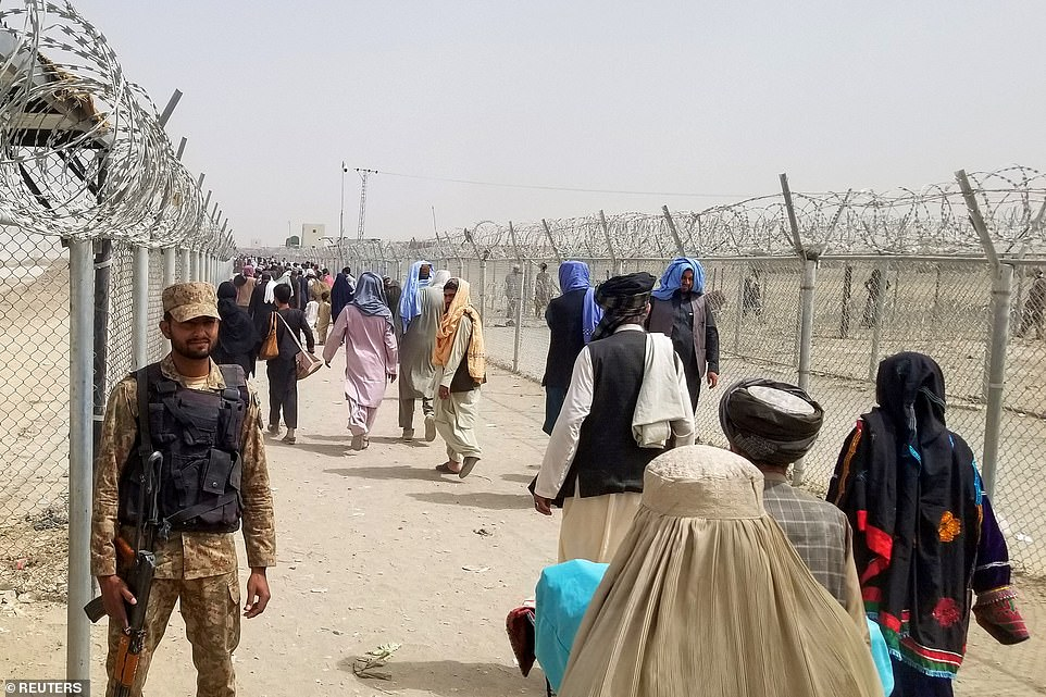 Pictured:A Pakistan's army soldier stands guard as people arriving from Afghanistan make their way at the Friendship Gate crossing point at the Pakistan-Afghanistan border town of Chaman, Pakistan August 16, 2021
